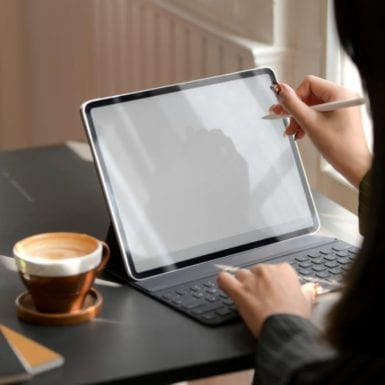 Close up view of female working on mock up digital tablet with stylus and coffee cup on black table in comfortable workplace
